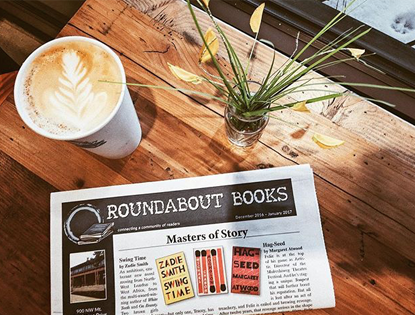 Photograph of Matchbook Marketing's Newsletter on an independent bookstore's table with a flower arrangement and a latte.