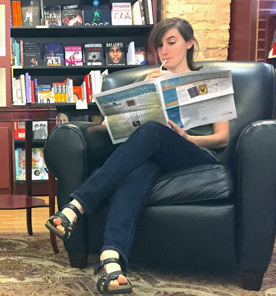 An independent bookstore customer reads a printed edition of Matchbook News. She is sipping a drink through a straw and looking down. There are shelves full of books in the background.